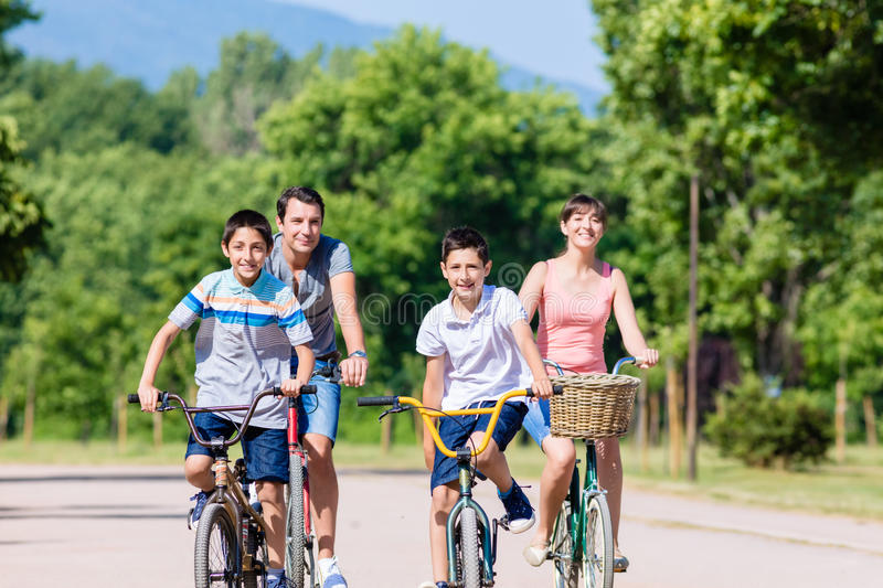 Family of four on bike tour in summer stock photography