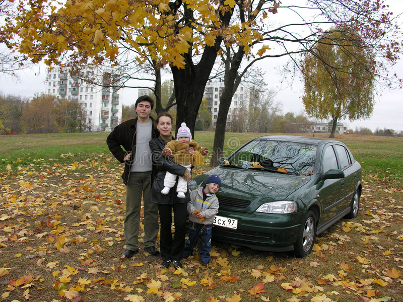 Family of four and car and autumn royalty free stock photography