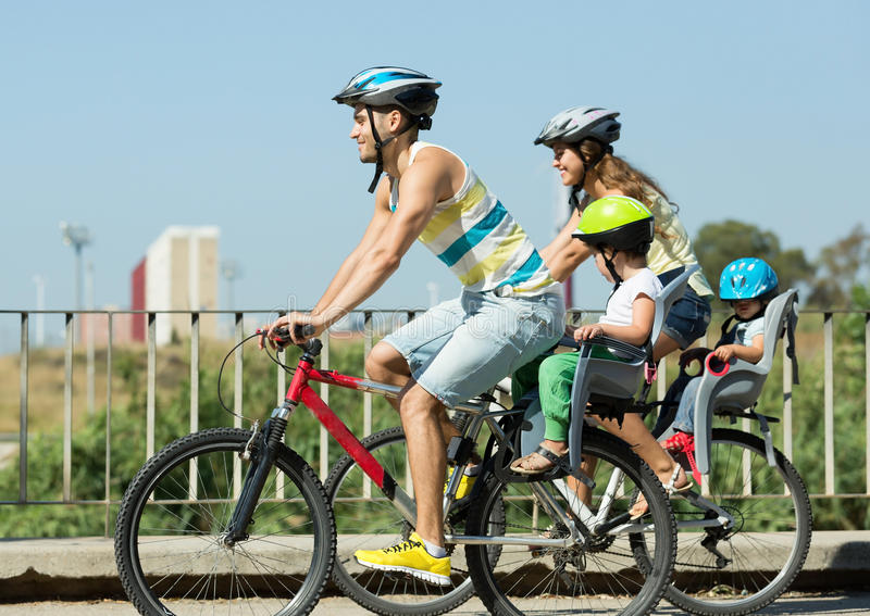 Family of four cycling on street. Active young family of four cycling on street road in summer day royalty free stock photos