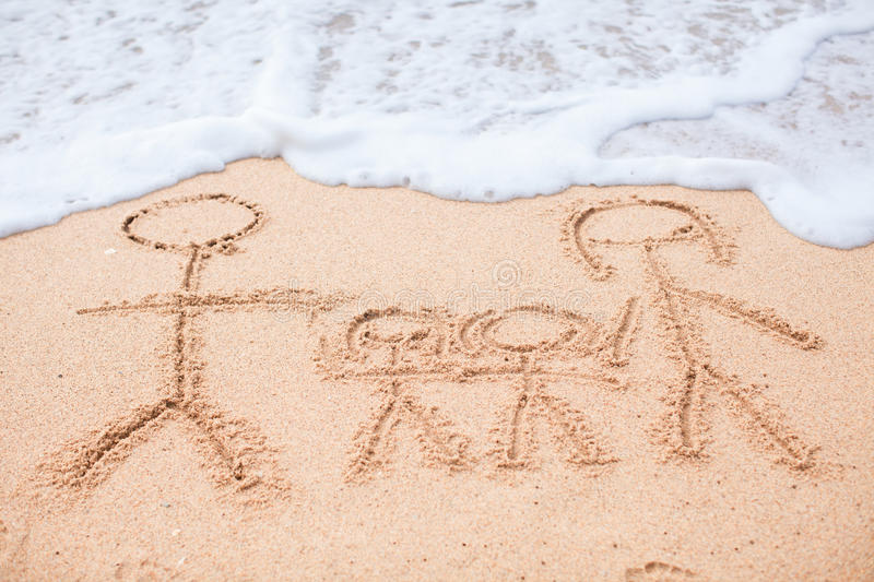 Family of four drawing on the beach. See my other works in portfolio royalty free stock images