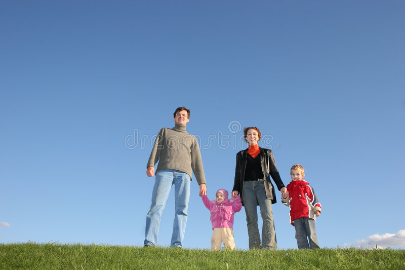 Family of four on grass stock photos