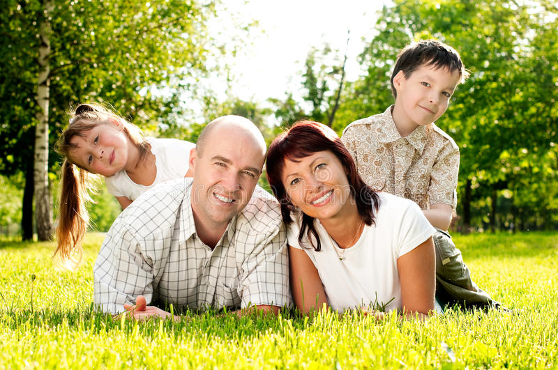 Family of four on grass royalty free stock photo