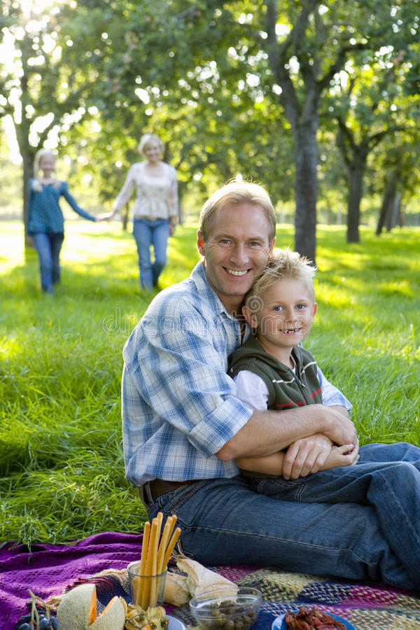 Family of four having picnic, father embracing son (7-9) smiling, portrait stock image