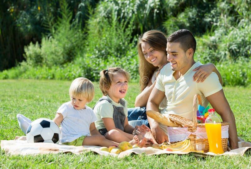 Family of four having picnic. Happy smiling family of four having picnic at meadow royalty free stock photos