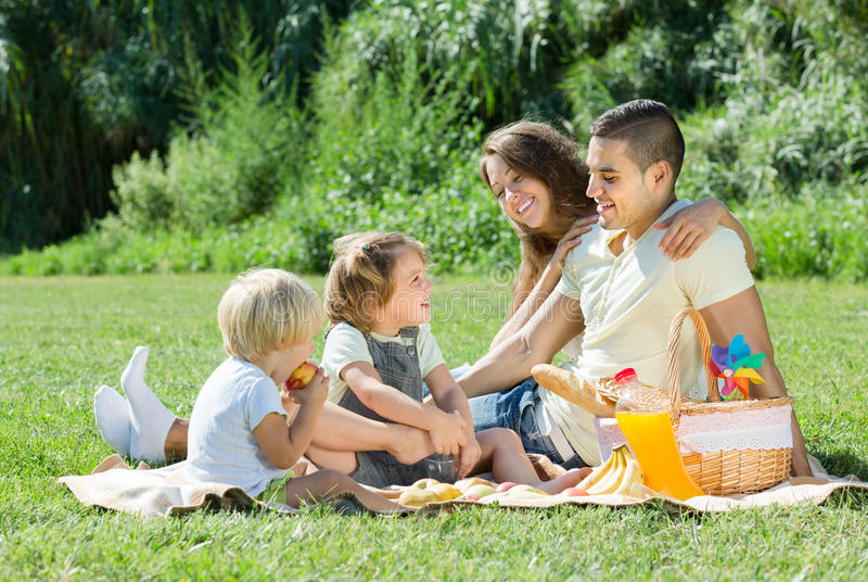 Family of four having picnic. Happy young family of four having picnic at meadow at summer day royalty free stock photography