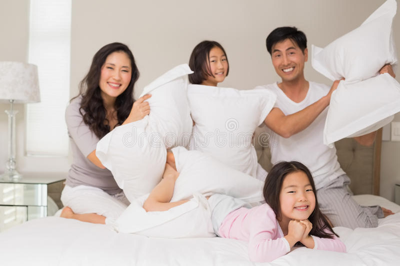 Family of four having pillow fight on bed stock image