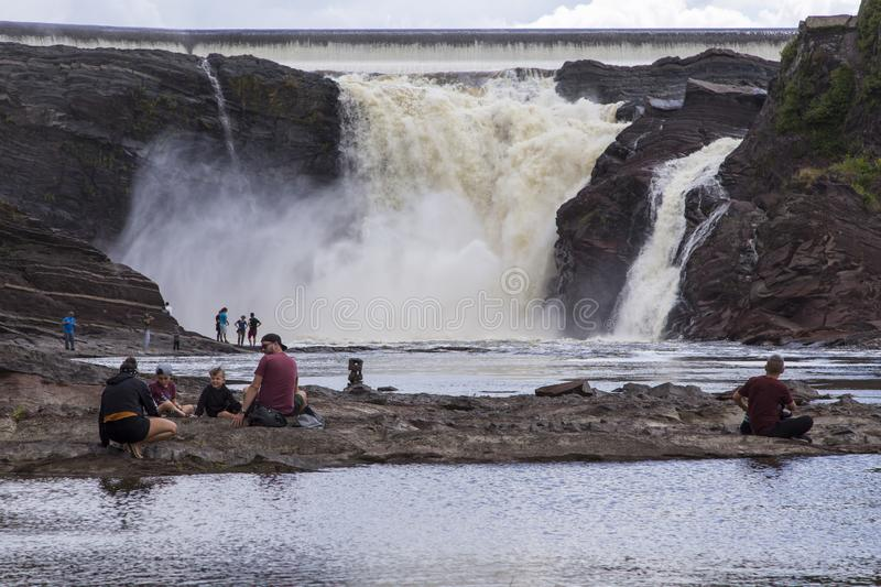 Family of four and other people enjoying the view of the impressive 115-foot tall Chaudière River Falls royalty free stock photography