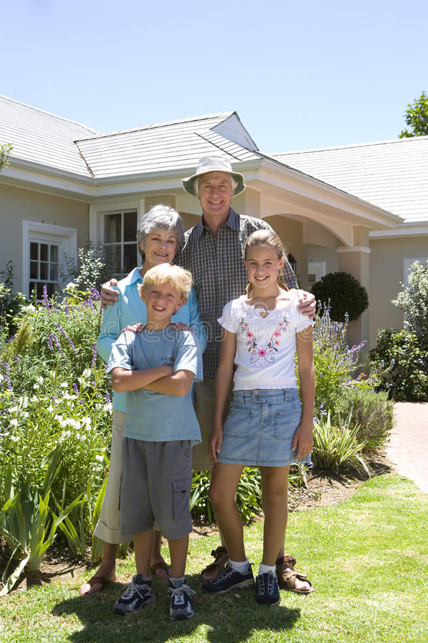 Family of four outside house, smiling, portrait stock photography