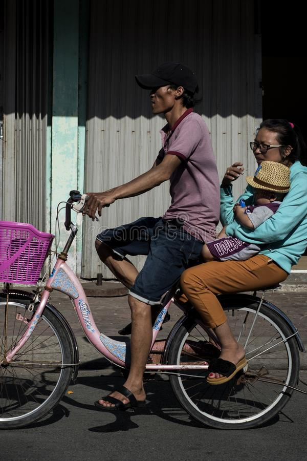 Family of four passes by on a bicycle in a street of Can Gio, Vietnam stock photo