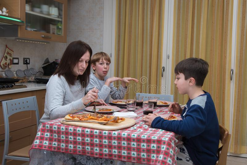Family of Four People Eating Pizza on the Kitchen Table at Home royalty free stock images