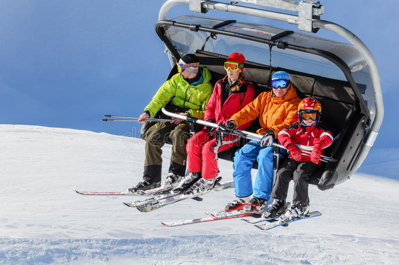 Family of four people riding on a chair ski lift royalty free stock photos