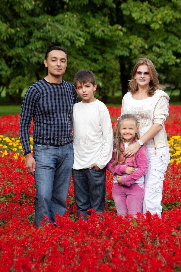 Family Of Four Persons In Flowering Park Royalty Free Stock Images