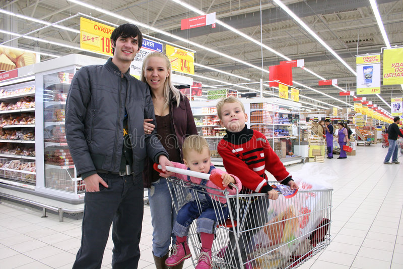 Family of four in shop. Family of four and carriage in shop stock images