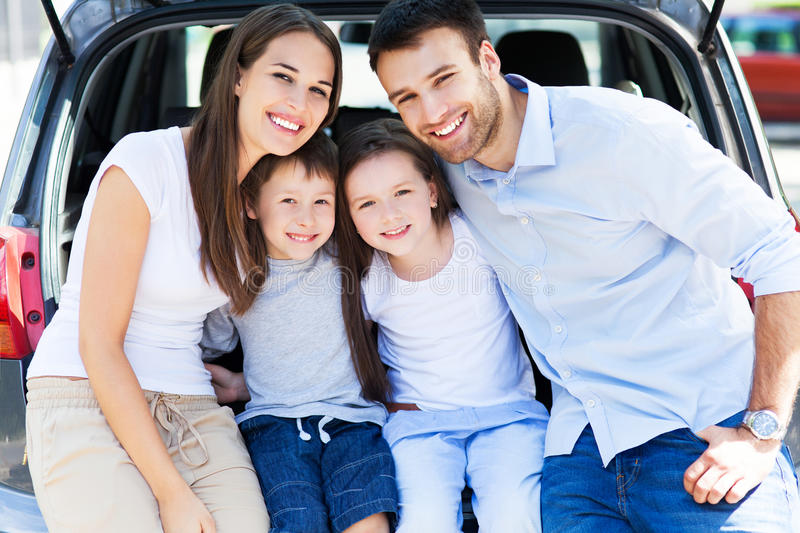Family Of Four Sitting In Car Trunk Stock Photo
