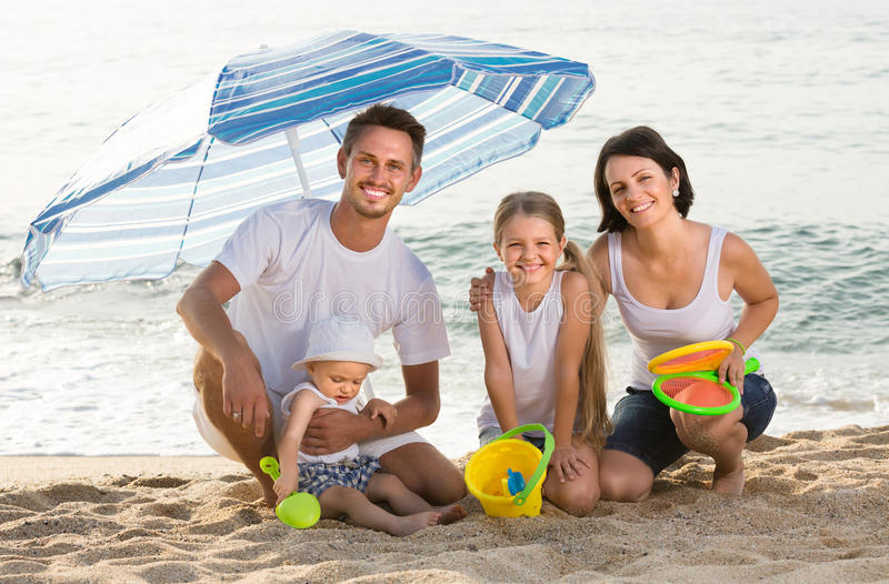 Family of four sitting together under beach umbrella on beach stock image