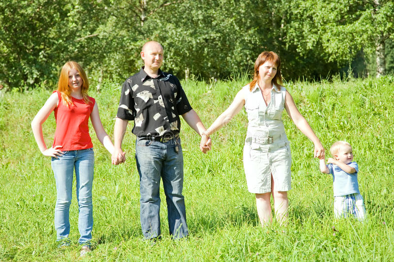Family from four stands on grass. Happy family from four stands on grass against nature royalty free stock photos