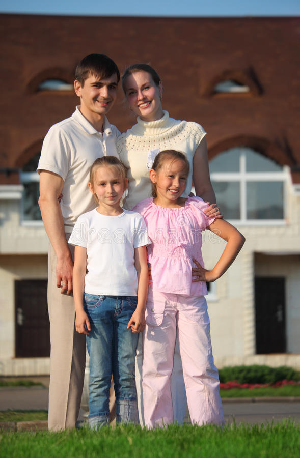 Family from four stands on grass against house. Family from four stands on green grass against house royalty free stock photo