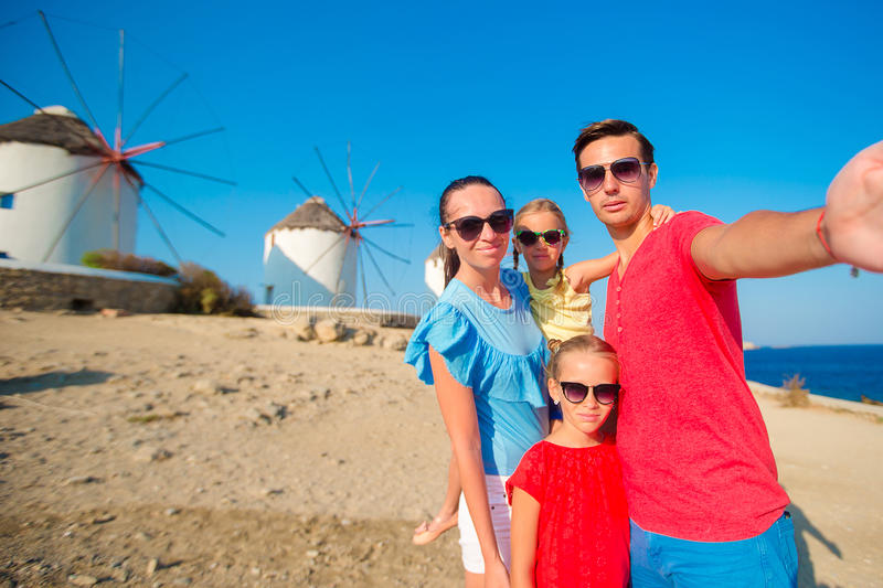 Family of four taking selfie with a stick in front of windmills at popular tourist area on Mykonos island, Greece. Family taking selfie with a stick in front of stock photos