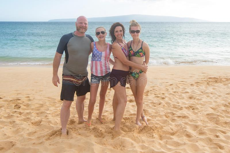 Happy family of four at a tropical beach vacation. Family of four together on sandy ocean beach stock image