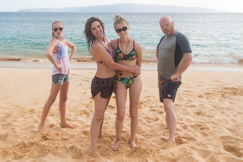 Happy family of four at a tropical beach vacation. Family of four together on sandy ocean beach stock photo