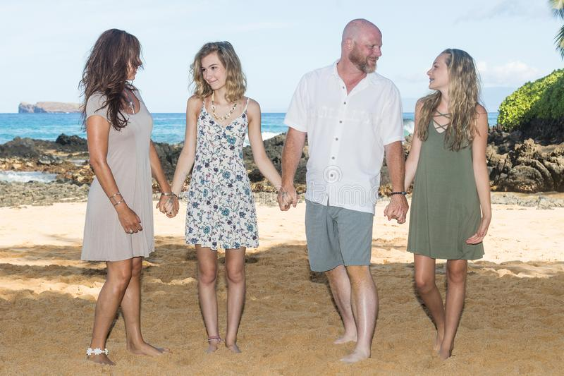 Happy Family together at the beach. Family of four. Two parents and two kids in Hawaii holding hands royalty free stock images