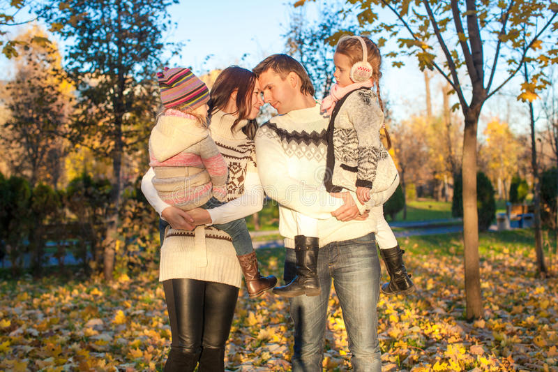 Family of four walk in autumn park on a sunny warm royalty free stock photography