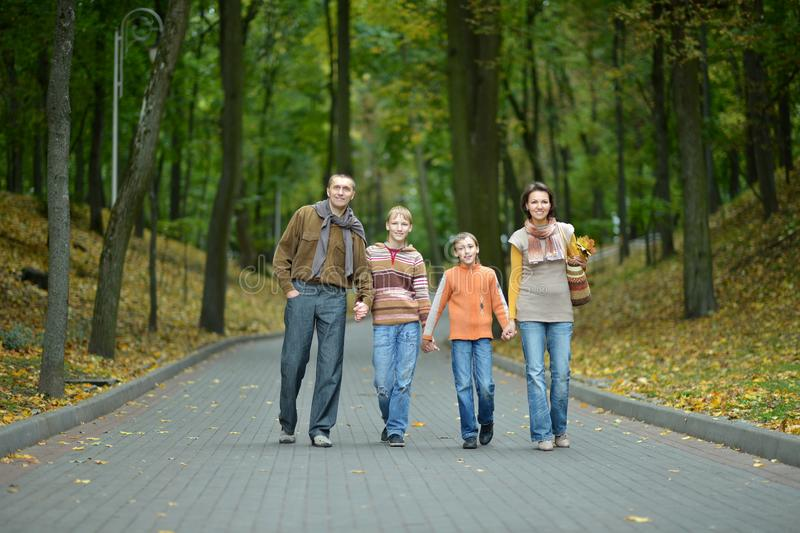 Family of four walking in autumn park royalty free stock photography