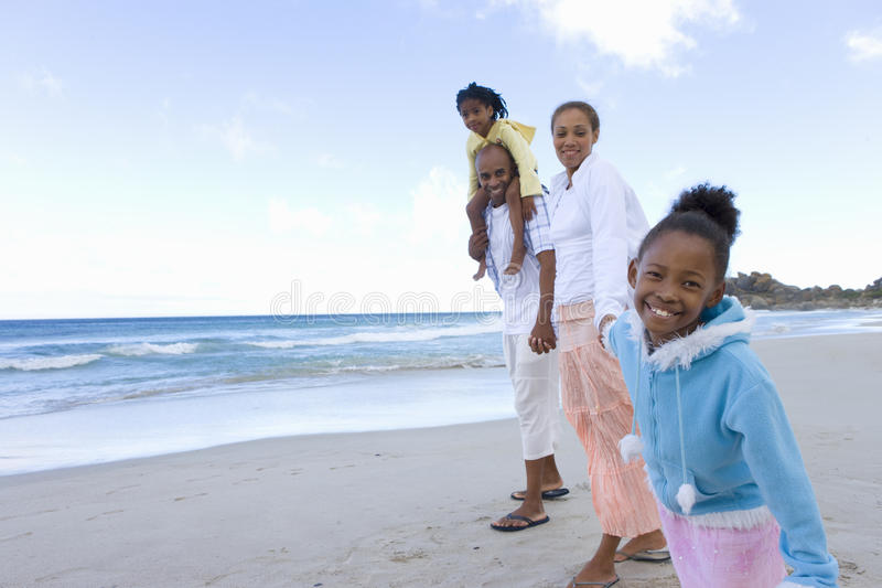Family of four walking on beach, portrait of girl (7-9) smiling, low angle view stock images