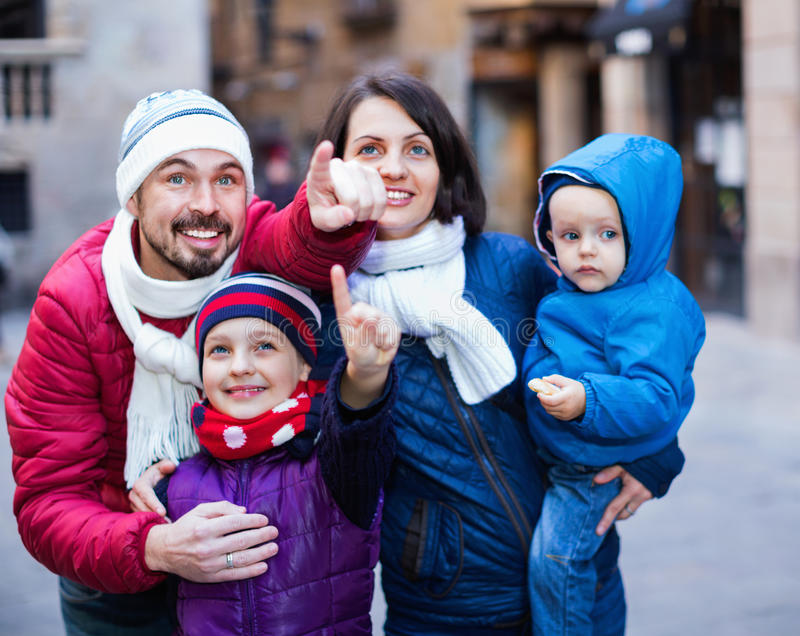 Family of four walking in city and looking showplace royalty free stock image