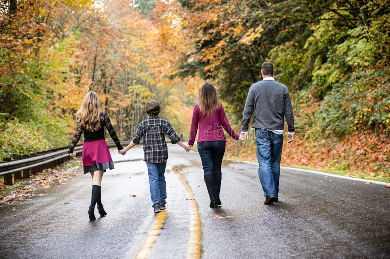 Family of four walking down a wet road holding hands. royalty free stock photography
