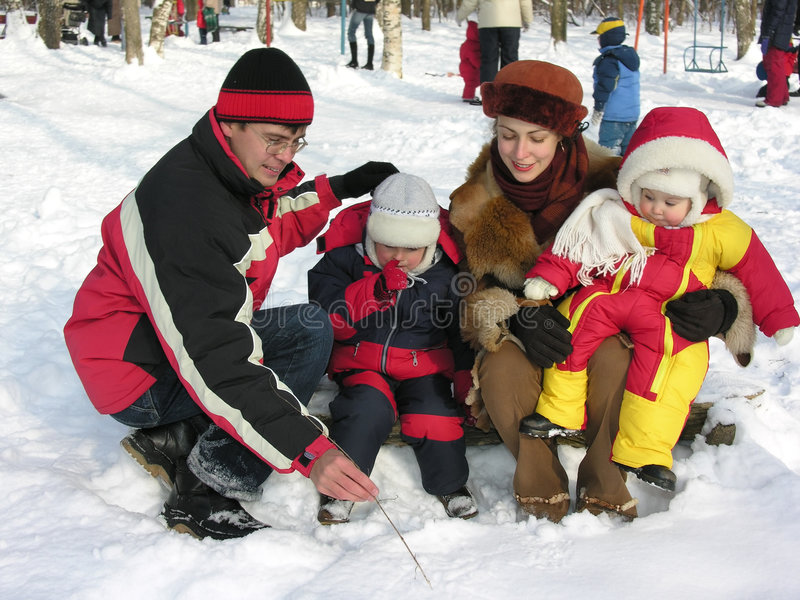 Family of four in winter park stock photography