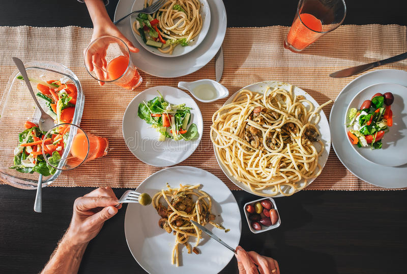 Family fresh dinner with grapefruit juice, pasta and salad stock image