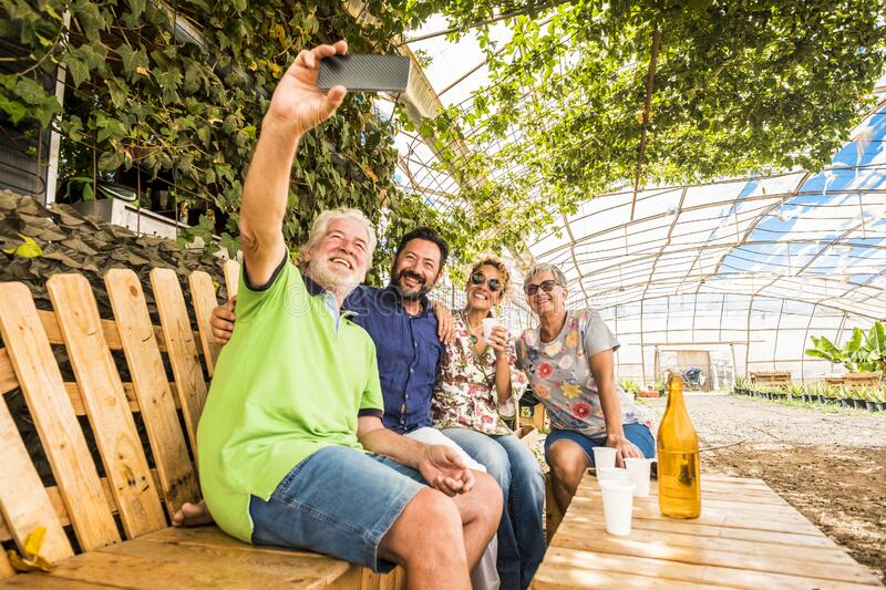Family and friends have fun all together in outdoor leisure activity sit down on a recycled wooden bench and taking picture selfie royalty free stock photo