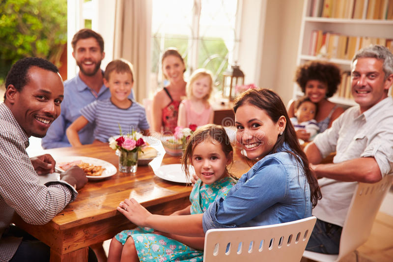 Family and friends sitting at a dining table, looking at camera royalty free stock photo