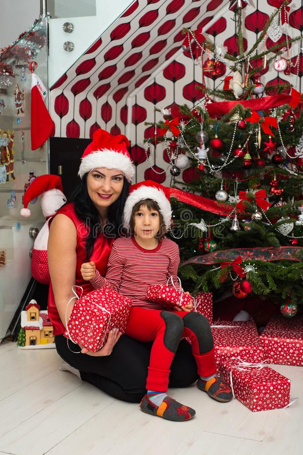 Family in front of Christmas tree. Cheerful family of mother and son posing together in front of Christmas tree in their home royalty free stock photos