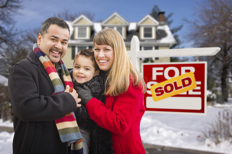 Family in Front of Sold Real Estate Sign and House. Warmly Dressed Young Mixed Race Family in Front of Sold Home For Sale Real Estate Sign and House with Snow On stock images