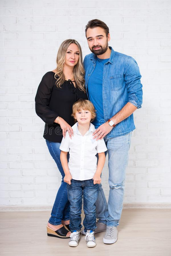 Family full length portrait - couple and little son. Over white brick wall stock photography