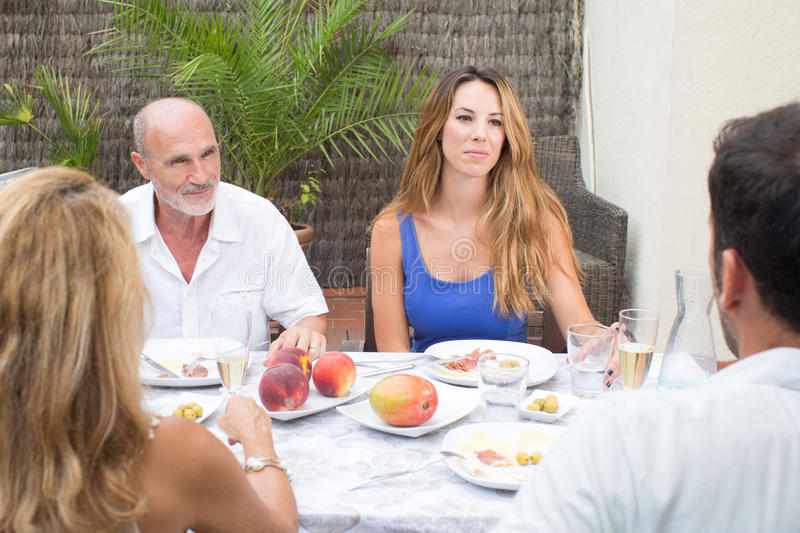 Family fun. Family during a conversation while having food in garden stock photo
