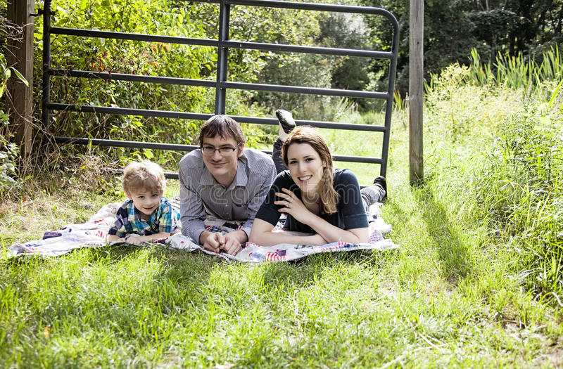 Family fun picnic. Happy parents with a boy laying on a blanket outside stock image