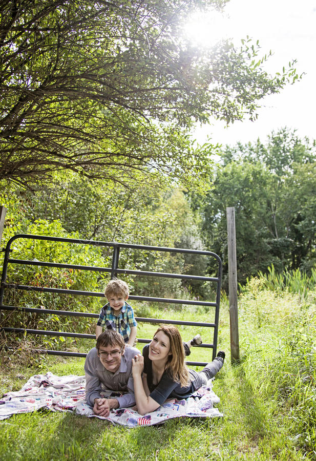 Family fun picnic. Happy parents with a boy laying on a blanket outside stock images