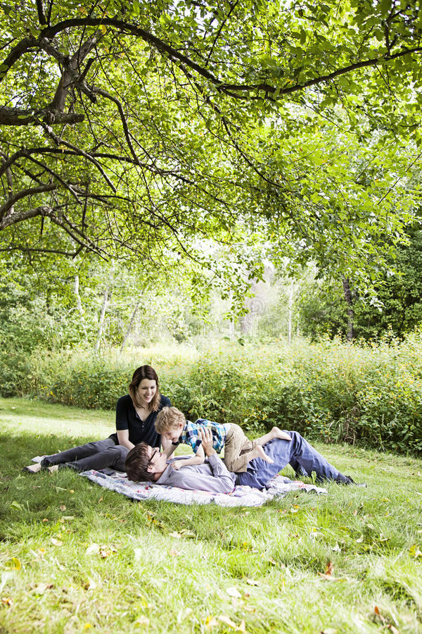 Family fun picnic. Happy parents with a boy playing on a blanket outside stock photography