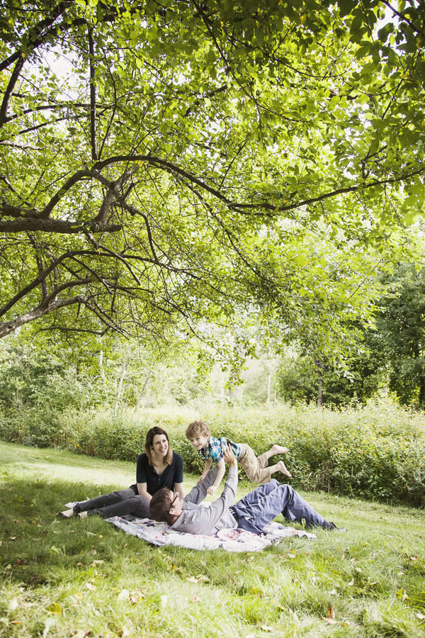 Family fun picnic. Happy parents with a boy playing on a blanket outside royalty free stock images