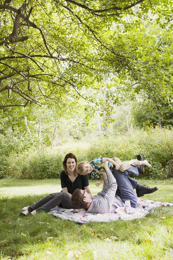 Family fun picnic. Happy parents with a boy playing on a blanket outside royalty free stock photo