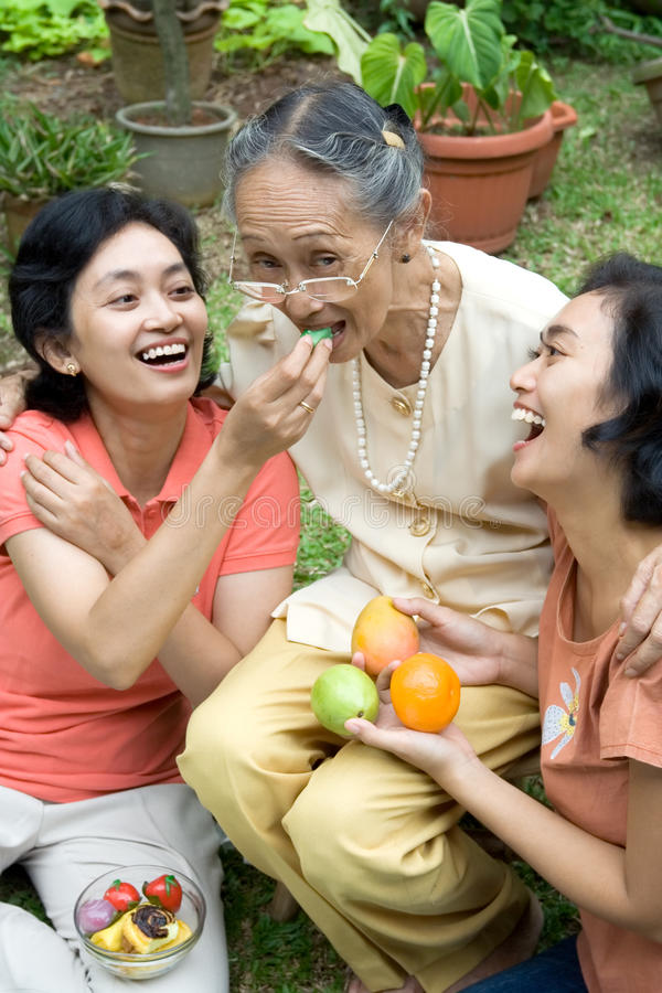 Family fun together. Portrait of cheerful asian family: an elderly mother having a quality time together with two of her daughter at home royalty free stock photos