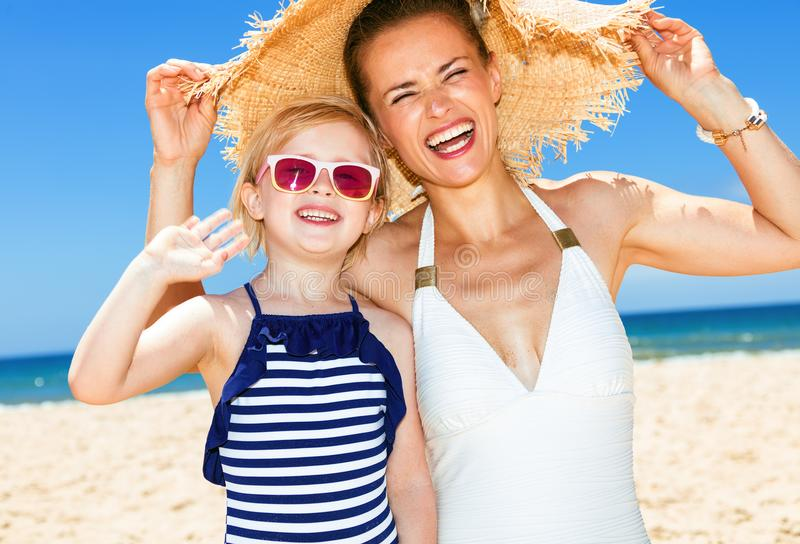 Happy modern mother and daughter on seacoast handwaving. Family fun on white sand. happy modern mother and daughter in swimwear on the seacoast handwaving royalty free stock images