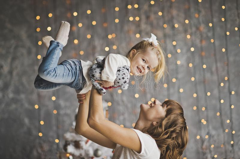Mother throws daughter on the background of sparkling lights royalty free stock photos