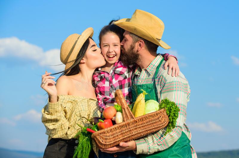 Family gardening. Family farm concept. Parents and daughter farmers celebrate harvest holiday. Family farmers hug kiss. Kid hold basket fall harvest. Family stock photography