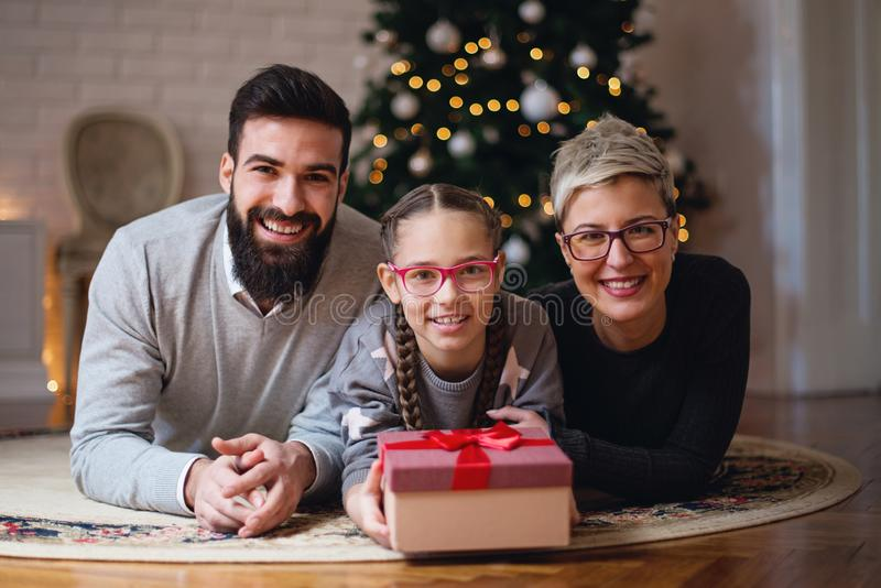 Family gathered around a Christmas tree; father, daughter and mother stock photos
