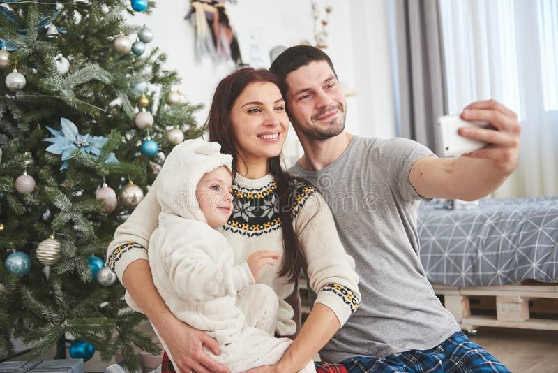 Family gathered around a Christmas tree, using a tablet royalty free stock images