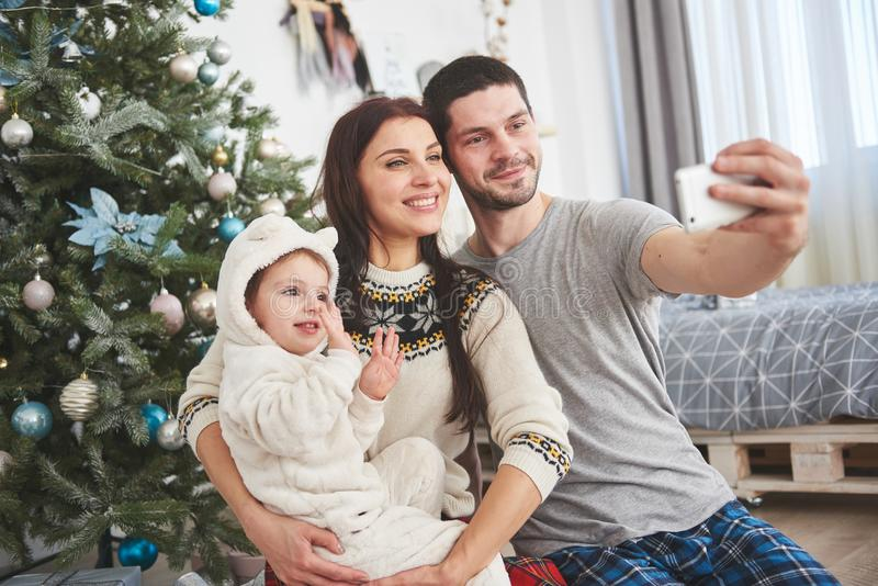 Family gathered around a Christmas tree, using a tablet stock photo